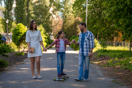 Smiling Family With Skateboard In Summer Park. Happy Parents Hodling Daughter Hand While She On Skateboard.