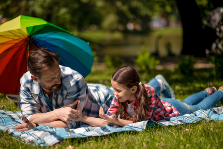 Father And Daughter Lying On Grass In Summer Park. Holding Hands. Colorful Umbrella Nearby. Happy Family Concept.