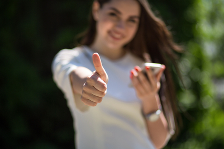 Beautiful Brunette Showing Thumb Up While Talking Over Phone In Summer Patk. Selective Focus On Thumb Up. Фото со стока