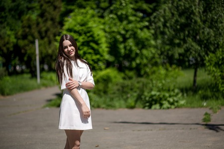 Young Smiling Brunette Woman In The Park Touching Her Right Hand With Her Left Hand. She Is Wearing A White Dress And A Silver Watch. Lady Has Got Red Nails.Green Plants And Trees On The Background. Фото со стока