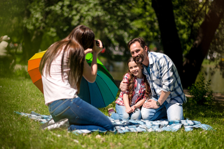 Young Mother Making Photo Of Husband And Daughter In The Park. Father Is Hugging His Daughter While Sitting On The Blanket And Smiling.Colorful Umbrella Is Next To Them.