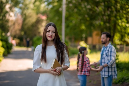 Young Woman Is Holding The Book While Standing In The Park.Her Hasband And Daughter Holding Each Other Hands And Making Circle On The Background. A Figure Of Woman Backgroung. Фото со стока