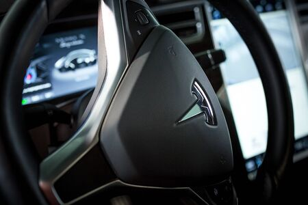 Modern Technologies in Tesla Electromobile. Close-Up Steering Wheel with Metal Elon Musks Tesla Emblem. Future Vehicle. Kyiv, Ukraine, F-Drive showroom 13 of february 2018.