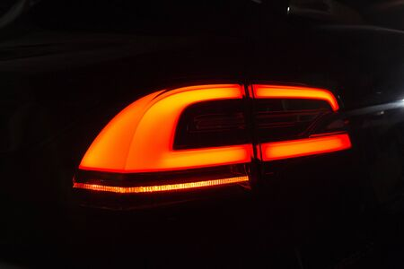 Bright Orange Rear Light of Beautiful Tesla Model X. Tail Lights of New Electro-Hybrid Automobile. Kyiv, Ukraine, F-Drive showroom 13 of february 2018.