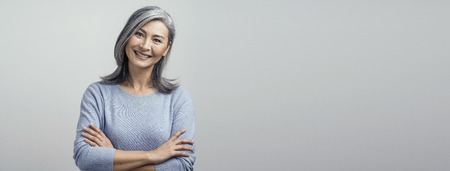 Portrait Of Happy Woman With Broad Smile And Crossed Arms. Cute Asian Grey-Haired Woman Broadly Smiles And Crossed Her Arms White Posing At Studio. Reklamní fotografie