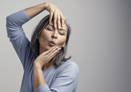 Beautiful Grey-Haired Woman Does Model Posing For The Camera. Charming Middle-Aged Asian Woman Touching Her Face With Hands While Posing At The Photo Studio.