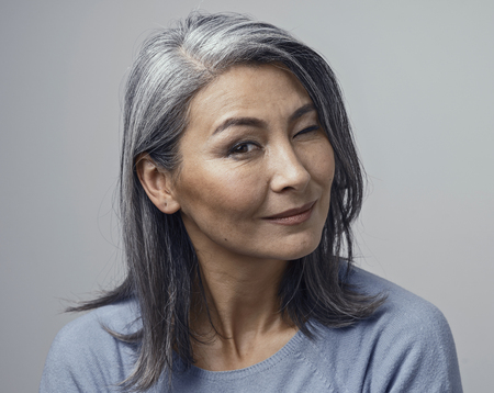 Cheerful Senior Woman Winks And Smiles At Camera. Portrait Of Beautiful Asian Woman With Grey Hair Winking With One Eye And Smiling. Stock Photo