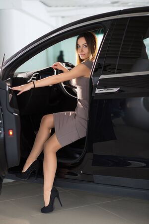 Sexy Woman is Sitting on Front Seat of Electric Tesla Automobile and Looks at Camera Cocketishly. New-generation Electric Vehicle Technology.Kyiv, Ukraine, F-Drive showroom 13 of february 2018.