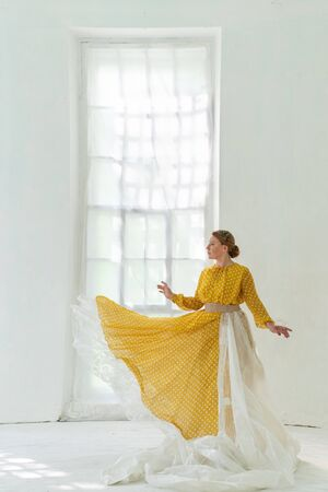 Yellow Dress on a Beautiful Middle-aged Woman. Dancer Performs Pa in the White Room on the Background of the Window.