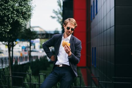 A Male Office Worker In Dark Sunglasses Sits Outside In The Summer And Eats A Burger At Lunchtime. A Young Man Rushing To Eat His Food And Hurries To Work. Business Concept Photo