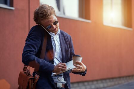 A Serious And Attractive Guy In A Suit Speaks On The Phone With A Client And Writes Information On Paper. A Man Works On The Go While On The Street. Business Concept Photo