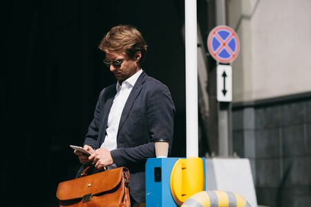 A Businessman Is Standing In A Parking Lot And Reading News On A Mobile Phone. A Man In A Suit Got Out Of The Car And Waits For The Start Of The Working Day. Business Concept Photo Banco de Imagens