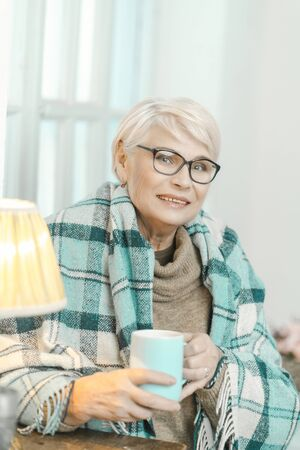 Senior Woman Wearing Glasses Is Wrapped In A Checkered Plaid To Feel Comfortable. Granny Is Drinking Tea. Switched-on Lamp Is Next To Her.