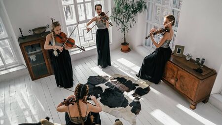Quartet Of Classical Female Musicians Playing Iside Spacy And Well-furnished Room. Women Are Wearing Beautiful Dresses. They Are Playing Violin And Cello. High-Angle Shot. Standard-Bild