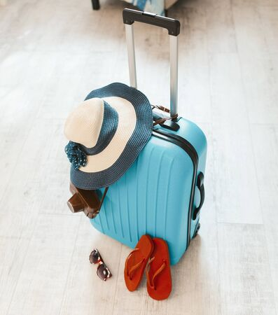 Top view of blue suitcase packed for summer vacation. Suitcase with hat and havaianas.