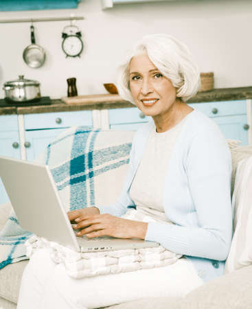 White haired italian senior woman use laptop to update her social media or text for her new cooking blog, show sitting on a white furniture next to kitchen background Stockfoto