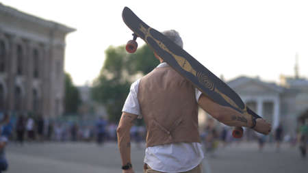 A Light-Skinned Middle-Aged Skater Walks Through The Town Square Holding Longboard On His Shoulder. View From The Back. The Sky And Architecture On A Blurred Background. 免版税图像