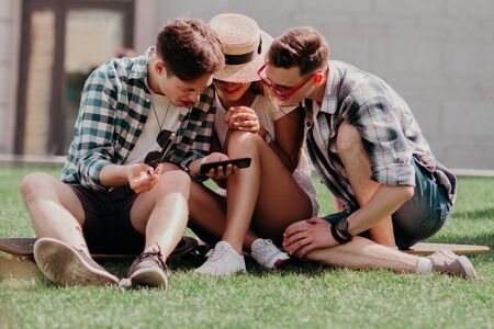 The Youngsters Leaned Together Over A Mobile Choosing The Best Photo Sitting On The Grass On A Summer Day. Stylish Young People In Casual.