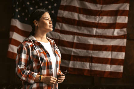 Patriotic Citizen Pondered Looking To Sideaway, A Beautiful Asian Woman In A Plaid Shirt Holding Glasses And Smiling On Americas Flag Background