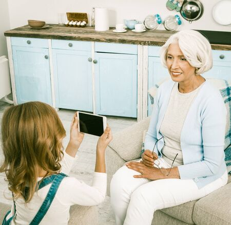 Grandmother Posing For New Mobile Or Smart Phones Camera While Sitting On White Sofa Happy White Haired Granny Smiling While Making Photos, Or Videos By Her Granddaughter Stock fotó