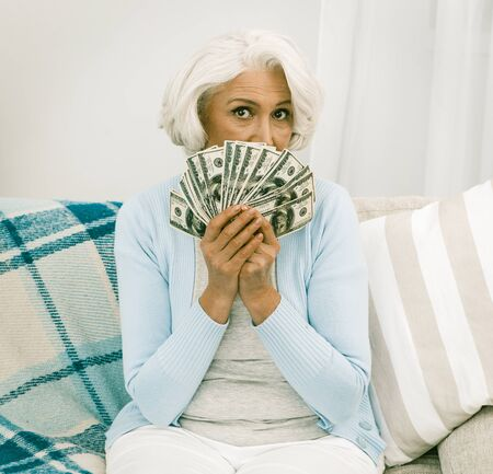 Mature Woman Covered HerFace With A Fan Of Dollar Bills While Thinking How To Distribute Inheritance, Elderly Woman Holding Much Money In Her Hands While Sitting On Sofa Or Couch
