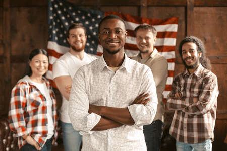 Smilling Multi-National Group Of Young American Patriots Poses Against The Background Of A Wooden Wall With Americans Flag, Selective Focus On African-American Man In Front 免版税图像