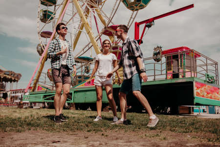 Friends Students Have Fun Together In The Park. Young Guys And A Girl Rejoice Together Against The Background Of The Ferris Wheel 免版税图像
