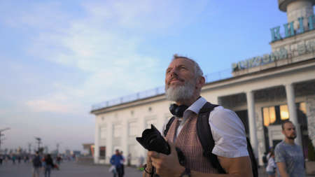 The Middle-Aged Man Dreamily Stopped To Admire The Beautiful View Of The City And Looks Up With The Camera In His Hands