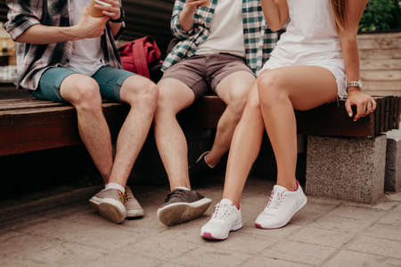 Three Light-Skinned Guys With Paper Glasses Rest Sitting On A Bench While Walking Around The City. A Group Of Friends In Kejual And Sneakers Rest And Drink Tea And Coffee. Teenagers Legs Close Up. 免版税图像