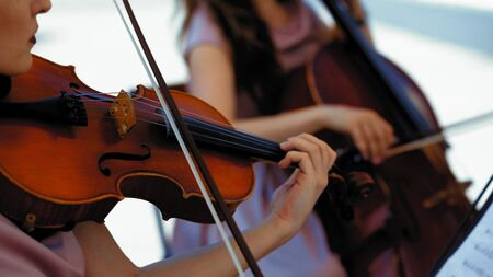 Musical Orchestra Of Female Musicians Plays On The Summer Terrace Outside, Hands Holding A Violin And Bow, Close Up