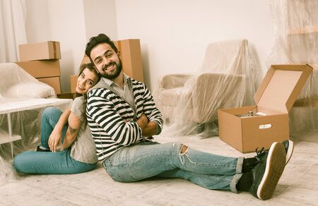 Young Man And Woman Are Tired After Preparation For Relocation, Couple Sitting On The Floor Back To Back Relaxing After Packing Boxes For Movin In New Apartment, Toned Image