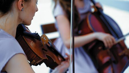 Musical Band Of Female Musicians Plays On Event Outdoor, Hands Holding A Violin And Bow, Close Up Cello on Blurred Background Фото со стока