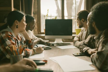 Diverse Ethnicity Team Of Young Business People Looking On Computer Screen, Multi-Ethnic Group Of Coworkers Talking While Sitting At Table In Sunny Coworking Space, Side View Standard-Bild