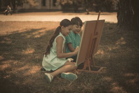 Two Cheerful Kids Drawing In Nature Outdoor, Happy Children, Boy And Girl, Drawing Or Writing On Art Board Outside In Sunny Summer Day In City Garden, Toned Image