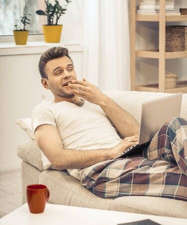 Relaxation At Home During Quarantine, Caucasian Man In Pyjamas Lying On Couch And Yawning, Bored Man In Casual Wear Is Lying On Sofa While Using Laptop, Toned Image