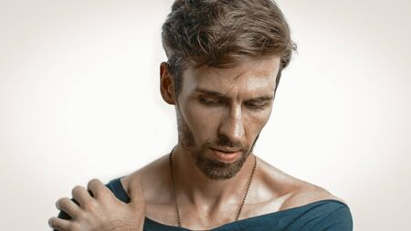 Close-Up Portrait Of A Handsome Pensive Man, A Caucasian Man In A Black T-Shirt With A Wide Neckline Lowered His Gaze Down With His Hand On His Shoulder, Emphasized Focus On Male Face