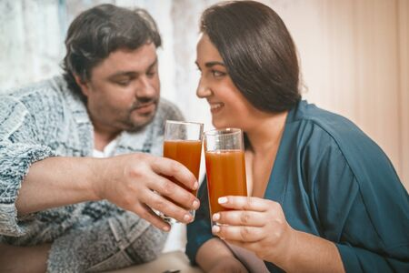 Body Positive Man And Woman Clinking With Glasses Of Orange Juice, Caucasian Couple Casual Clothing Flirting And Joining With Glasses While Sitting At Home