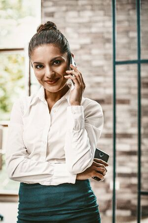 Charming Businesswoman Speaks Ower Phone Looking Into Camera, Smiling Business Lady In Formalwear Talks By Mobile Holding Smartphone In Her Other Hand While Standing In Modern Office, Toned Image