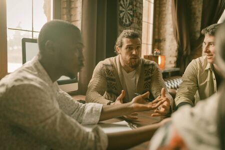 Creative Multi-Ethnic Team Of Freelancers Discussing Startup Project, Colleagues Arguing Each Other Sitting At Table And Gesticulating With Hands In Backlit, Focus On Caucasian Man