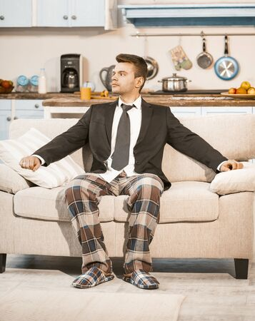 Bored Businessman Awaiting Quarantine Ending At Home, Serious Caucasian Man In Elegance Business Jacket And Pajama Pants Sits On Sofa Looking At Window, Work From Home, Toned Image