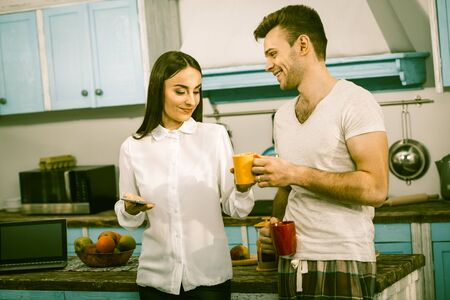 Loving Couple Spends Time Together, Caring Husband Giving Cup Of Hot Drink To His Wife, Sunny Morning In The Home Kitchen, The Joys Of Working From Home, Toned Image Archivio Fotografico