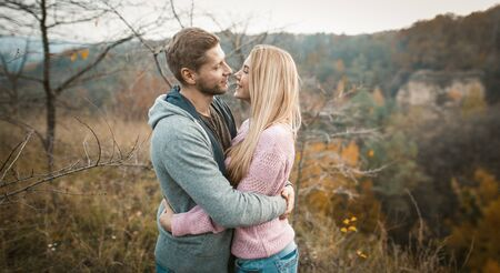Lovely Couple Of Travelers Stands Embracing On Cliff Edge Outdoors, Smiling Man And Woman Are Hugging And Looking At Each Other While Standing Against Background Of Autumn Nature