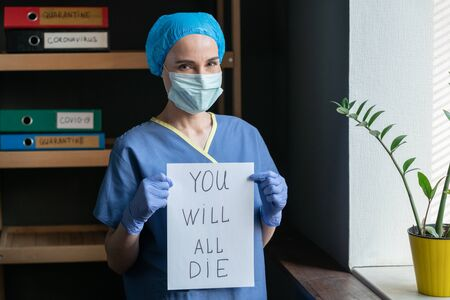 Female Doctor Showing Bad Prediction, Woman In Protective Mask With Sarcastic Look In Eyes Holding Poster That Says YOU WILL ALL DIE, Pandemic Concept Stok Fotoğraf