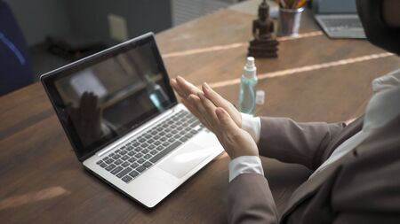 Business Woman Applies Disinfectant Spray To Disinfect Her Hands Before Working On Laptop, Preventive Measures For Disinfection When Working With Computer During Coronavirus Epidemic, High Angle View Banque d'images
