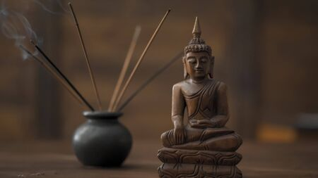 Wooden statuette of Buddha incense sticks at workplace. Abstract picture of a modern office in oriental style, selective focus on smoking incense sticks and wooden buddha figurine at table. Stock Photo