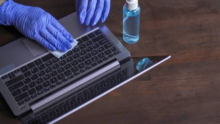 Disinfection of a computer keyboard. Hands in gloves carry out antiseptic processing of work surfaces. Necessary preventive measure in the fight against the coronavirus pandemic. Stock Photo
