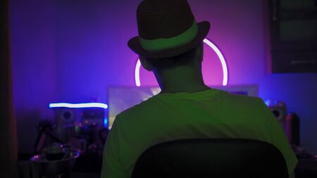 Rear View Of Man In Hat Working with computer Sitting At Home Work Place With Neon Glows, Self Isolation Quarantine Concept, Work from Home Concept.