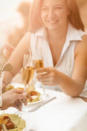 愉快的妇女微笑着拿着杯白葡萄酒。成熟夫妇有事件户外在海滩咖啡馆。在人的手上的选择聚焦有杯酒或香槟在前景。被定调子的图像。