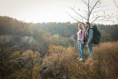Couple of tourists admiring the sunset standing on the edge of a cliff holding hands, a Caucasian young man and woman standing in nature in the rays of the setting sun, side view. Hiking concept. Banque d'images