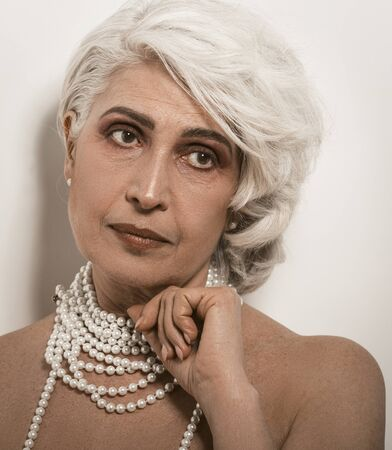 Stylish senior woman with well-groomed skin on white background. Mature woman with pearl beads touches her chin with hand looking at side. Beauty concept. Care for mature skin concept.